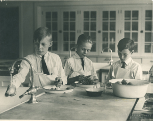 "This photograph shows three young boys preparing food during a child nutrition class hosted by the College of Human Ecology. A typed caption on the back of the photograph reads: ""Child Nutrition Class - 1925"" Originally from: http://onthebanks.msu.edu/"