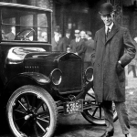 Henry Ford poses next to his Model T